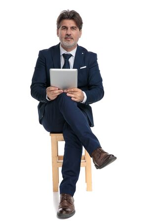 brown haired formal business man with navy suit is sitting with legs crossed holding his tablet and looking at camera happy on white studio background