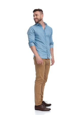 side view of a young casual man with blue shirt standing and looking back over shoulder happy on white studio background Banco de Imagens