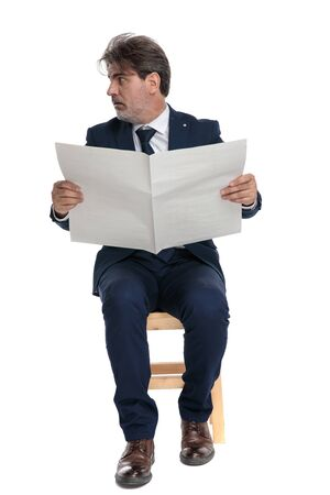 handsome formal business man with navy suit is sitting and holding a newspaper  shocked while looking to a side on white studio background