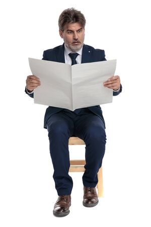 gorgeous formal business man with navy suit is sitting and reading the newspaper with big eyes shocked on white studio background