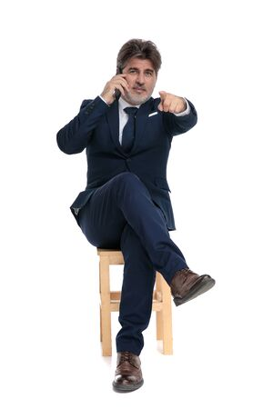handsome formal business man with navy suit is sitting with legs crossed and talking on the mobile phone while pointing forward confident on white studio background
