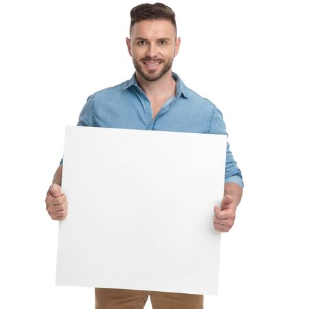 brown haired casual man with blue shirt is standing with a billboard on his hands happy on white studio background Stockfoto