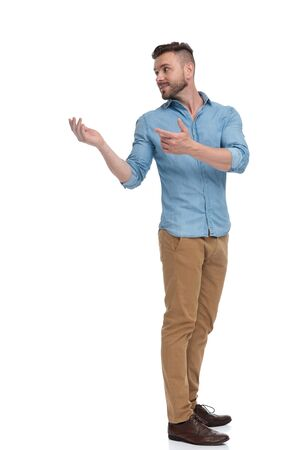 side view of a brown haired casual man with blue shirt standing with hands raised and looking back over shoulder intrigued on white studio background