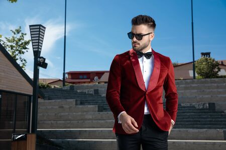 confident young elegant man wearing red velvet tuxedo and black sunglasses, holding hand in pocket, looking to side, outdoor in an urban scene Archivio Fotografico