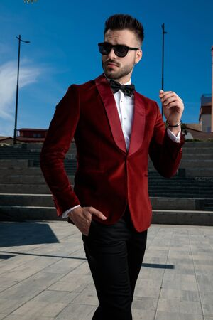 smart casual man wearing red velvet tuxedo and black sunglasses, walking and looking to side, holding hand in pocket, standing outdoor in an urban scene Archivio Fotografico