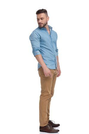vue latérale d'un homme décontracté en forme avec une chemise bleue debout et regardant par-dessus l'épaule pensif sur fond de studio blanc