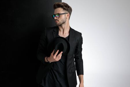 arrogant smart casual man wearing sunglasses and holding hat and looking to side, standing on black and white background in studio