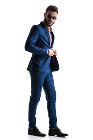 side view of a handsome formal business man in blue suit with beard and sunglasses walking and looking to a side while fixing jacket confident on white studio background