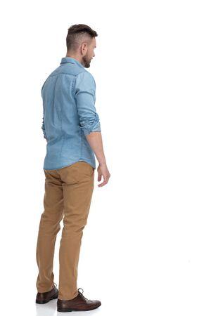 Vista trasera de un atractivo hombre casual con camisa azul de pie y mirando a otro lado pensativo sobre fondo blanco de estudio