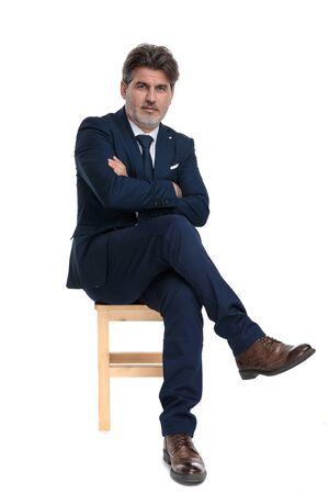 Attraktiver formeller Geschäftsmann mit Marineanzug, der mit verschränkten Armen und Beinen sitzt und zuversichtlich nach vorne blickt auf weißem Studiohintergrund