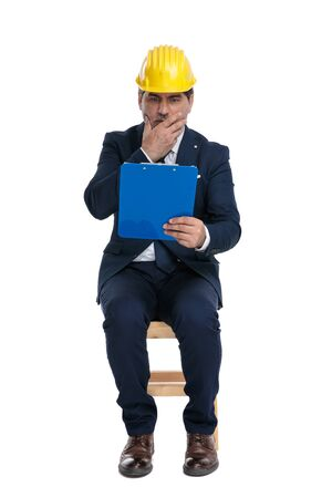 beautiful formal business man with navy suit and safety helmet is looking at his clipboard terrified on white studio background