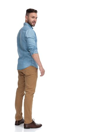 rear view of a casual man with blue shirt standing and looking back over shoulder cool on white studio background