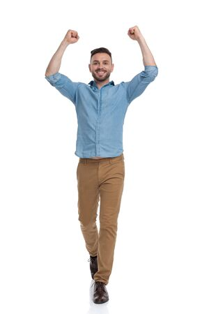 charming casual man with blue shirt walking with hands up in the air while looking ahead victorious on white studio background Archivio Fotografico