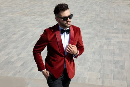 confident and sensual young man wearing red velvet tuxedo and sunglasses, holding collar and walking on white paving, outdoor in an urban scene