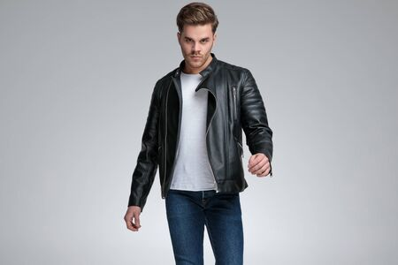 attractive casual man with black leather jacket is standing and looking at camera with a dominant attitude on gray studio background 版權商用圖片