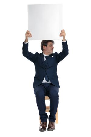 good looking formal business man with navy suit is sitting and holding a billboard overhead while looking to a side happy on white studio background