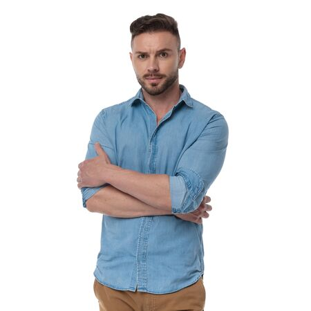 badass casual man with blue shirt standing with hands crossed confident on white studio background Stock Photo