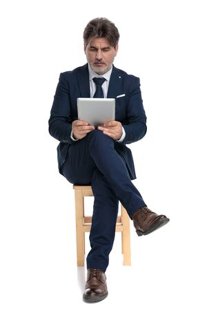 middle aged formal business man with navy suit is sitting with legs crossed and looking at his tablet engaged on white studio background Stock Photo