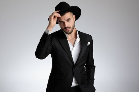 elegant young model wearing tuxedo, holding hat and saluting, on grey background in studio