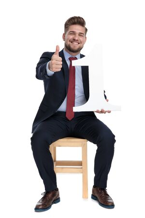 happy young businessman smiling, making thumbs up sign and holding number one sign, sitting isolated on white background in studio
