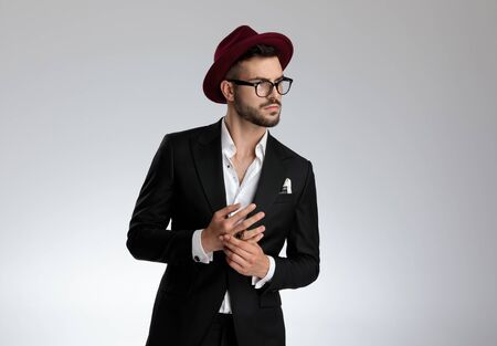 beautiful formal business man wearing a black suit,hat,glasses,ring is standing and looking to a side while holding hands pensive on gray studio background