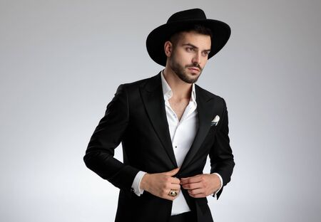 elegant attractive young man wearing tuxedo and black hat, arranging coat and looking to side, on grey background in studio