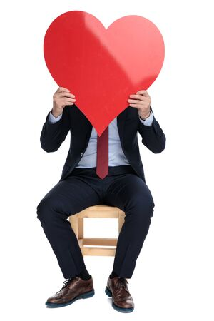 happy young businessman hiding behind big red heart, sitting isolated on white background in studio 版權商用圖片 - 130802988