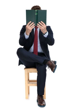 young businessman holding book and hiding behind the book, sitting isolated on white background in studio 版權商用圖片 - 130802846