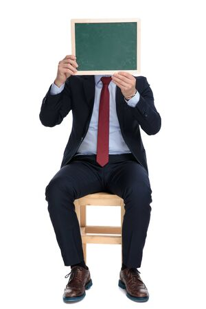happy young businessman holding blackboard and hiding behind it, sitting isolated on white background in studio 版權商用圖片 - 130802860