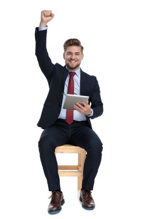 excited young businessman holding tab, smiling and holding hand up, sitting isolated on white background in studio 版權商用圖片 - 130802863