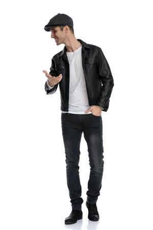 handsome casual man wearing a black leather jacket and hat standing with one hand in pocket and presenting while looking to a side happy against white studio background