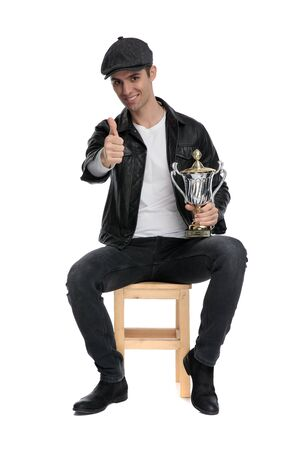charming casual man wearing a black leather jacket and hat sitting and holding his cup with a ok sign confident against white studio background Reklamní fotografie