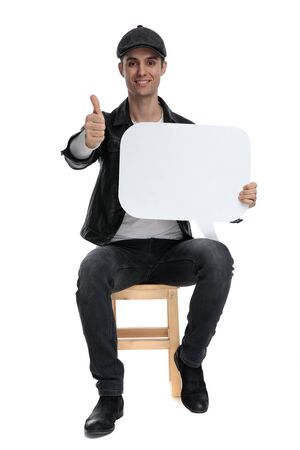 handsome casual man with black leather jacket and hat sitting and holding speech bubble while making ok sign gesture happy on white studio background