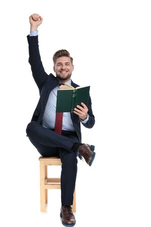 enthusiastic young businessman smiling, holding hand in the air and reading a book, sitting isolated on white background in studio 版權商用圖片 - 130802718