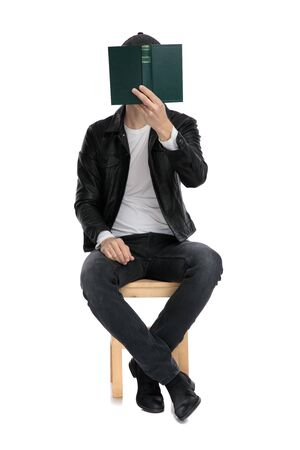 charming casual man wearing a black leather jacket and hat sitting and covering his face with a book against white studio background 版權商用圖片 - 130803116