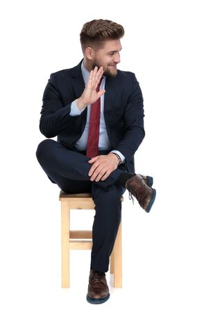 happy young businessman looking to side and waving, sitting isolated on white background in studio Stockfoto
