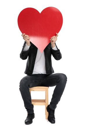 sexy casual man wearing a black leather jacket sitting and covering his face with a big red heart against white studio background