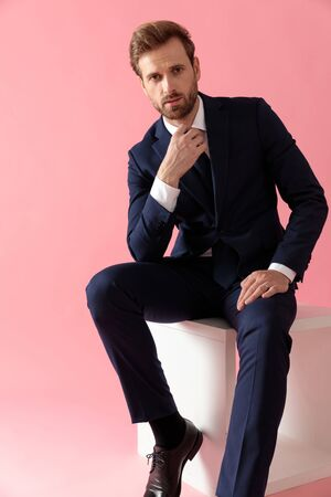 charming formal business man in navy suit sitting with one hand resting on his lap and fixing his tie while looking at camera confident on pink studio background