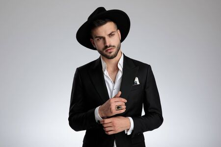 arrogant young model wearing tuxedo and black hat, arranging shirt and looking to side, on grey background in studio