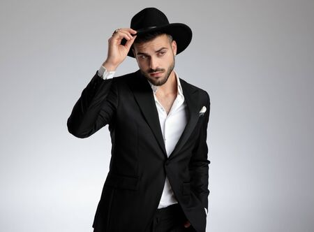 young elegant fashion model wearing black tuxedo, fixing hat and saluting, looking to side, on grey background in studio