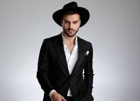 arrogant fashion model wearing tuxedo and black hat, holding hand in pocket, on grey background in studio