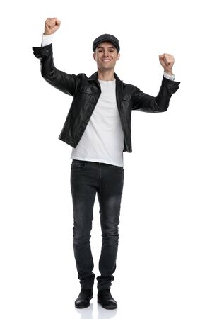 gorgeous casual man wearing a black leather jacket and hat standing with hands up in the air victorious against white studio background