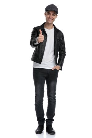 charming casual man wearing a black leather jacket and hat standing with one hand in pocket and a ok sign gesture happy against white studio background