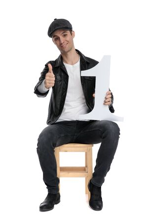 good looking casual man wearing a black leather jacket and hat sitting and holding a number one while making a ok sign confident against white studio background