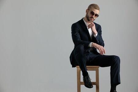Gut aussehender formeller Geschäftsmann, der einen Marineanzug und eine Sonnenbrille trägt, der mit einem Bein auf einem Stuhl sitzt und sein Kinn berührt, während er die Kamera nachdenklich auf grauem Studiohintergrund betrachtet looking