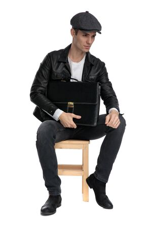 charming casual man wearing a black leather jacket and hat sitting and holding a briefcase while looking away pensive against white studio background