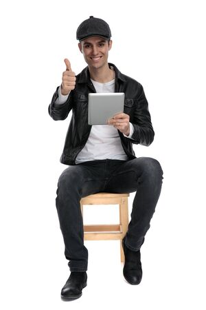 attractive casual man with black leather jacket and hat sitting and holding his tablet with a thumbs up gesture and looking at camera happy on white studio background
