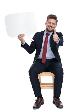 happy young businessman holding speech bubble and making thumbs up sign, sitting isolated on wooden chair, on white background in studio