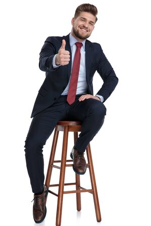 enthusiastic young businessman holding hands and making thumbs up sign, sitting isolated on white background in studio Reklamní fotografie