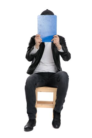 handsome casual man wearing a black leather jacket and hat sitting and covering his face with a blue clipboard against white studio background 版權商用圖片